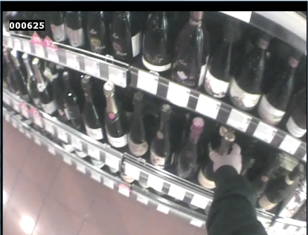 A consumer selecting wine in a shop